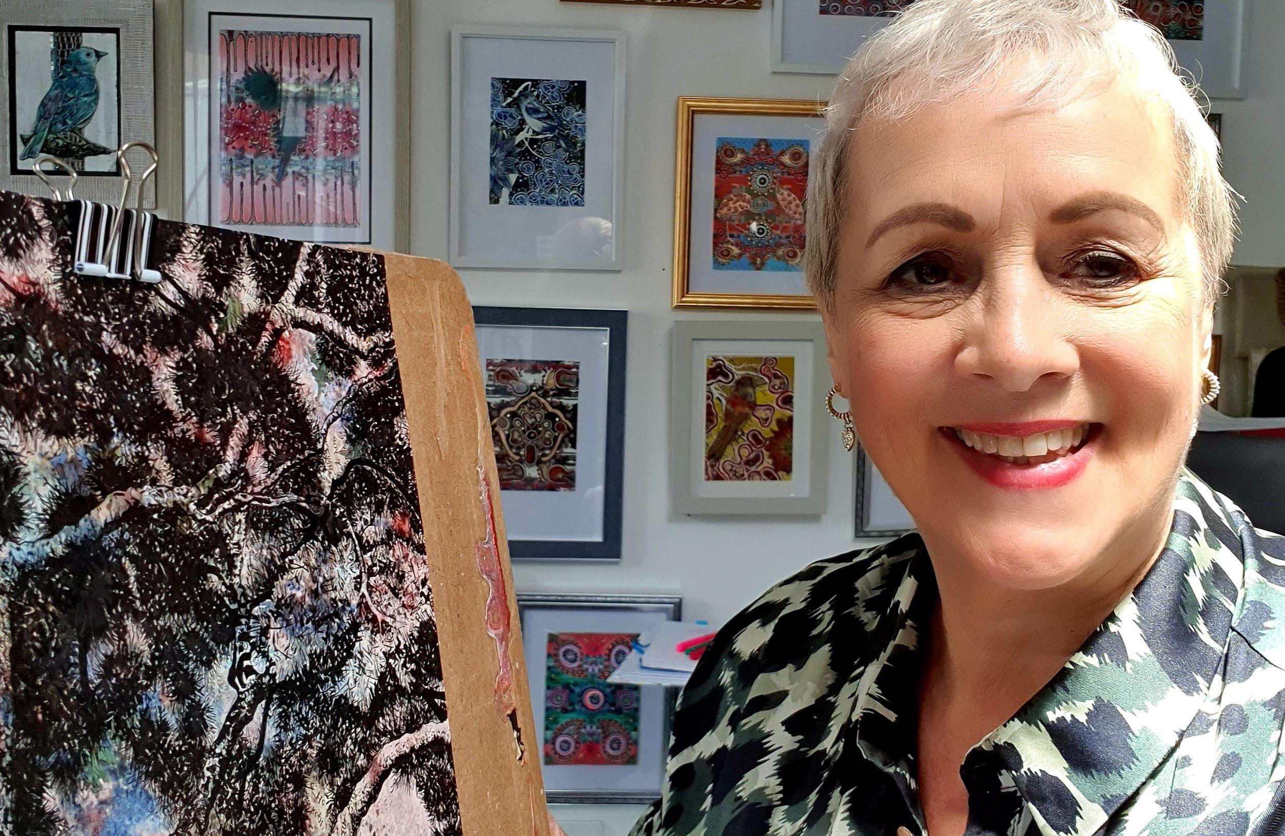 selfie of artist with paintings