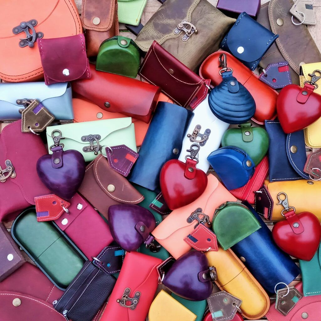 collection of small handmade leather purses, glasses case etc in lots of colours