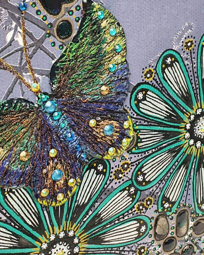 mixed media close up with embroidery butterfly and post pen flowers