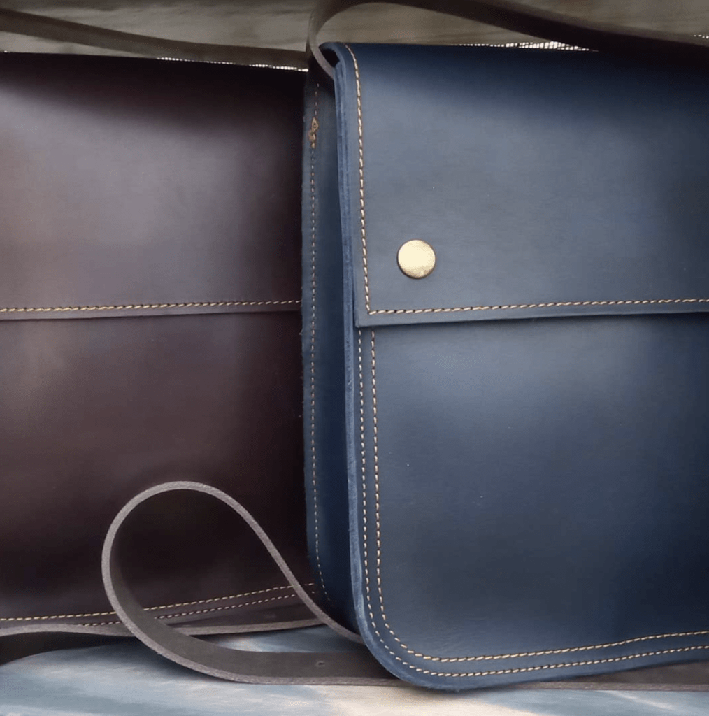 close up of 2 handmade leather messenger bags in navy and brown